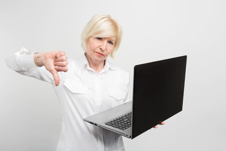 A picture of mature lady with new laptop. She has tested it and admitted the laptop is bad. Thats why she shows a big thumb down. Isolated on white background. Stock Photo