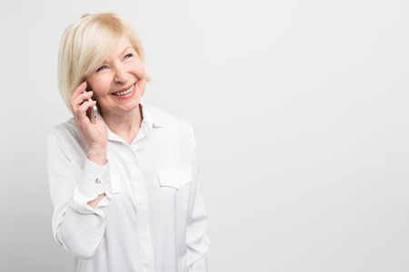 Nice picture of a lady calling t his family using a new smartphone. She adores new technologies and like to try to use new devices as much as she can. Isolated on white background.