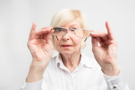 Close up of old woman is very attentive to details. She is looking to her glasses trying to find dirty spots there. She likes all things to stay clean. Isolated on white background.
