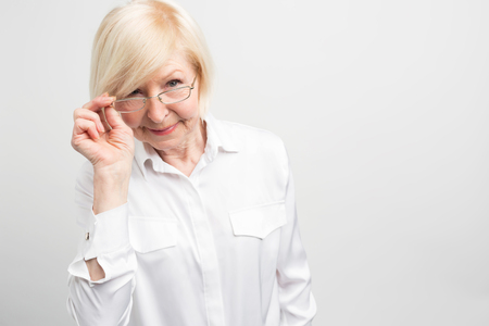 Cut view of mature woman that is holding one part of her glasses and looking straight forward. Sometimes old people can be too punctual and too annoying with contempting. Isolated on white background.