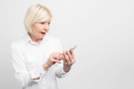 A picture of old lady holding new smartphone. She doesnt know how to use it properly because she didnt have anything like this phone before. Isolated on white background.