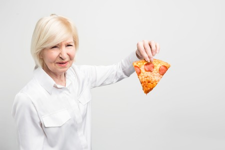 Grandma doesnt like the idea of eating this piece of pizza because it is not good and helthy for human beings. Isolated on white background.