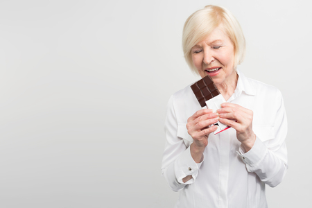 A picture of mautre lady eading a bar of milk chocolate. She likes to eat sweets. She cares about her health a lot but at the moment she wants enjoy taste of chocolate. Isolated on white background. Stock Photo