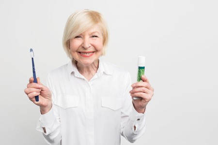 Cheerful and happy woman is holding a toothpaste and a toothbrush. She is showing her beautifyl smile. Isolated on white background. Stock Photo