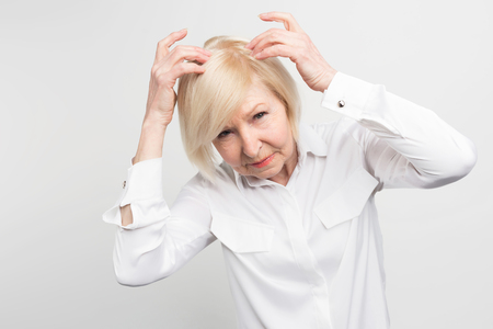 This woman has a problem of loosing hair from her head. She need some treatment. Otherwise she would need to start wearing a wig as soon as possible. Isolated on white background.