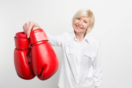 Joyful and nice old woman is holding boxing gloves in her right hand and smiling. She has what to do in her retirement. Isolated on white background.