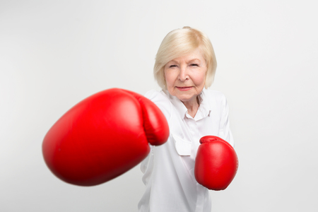 Serious woman is standing in position, wearing red boxing gloves. She is ready for doing some exercises. Isolated on white background.