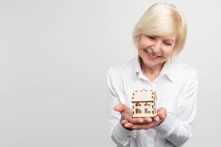 A picture of woman that has a small house-toy in her hand. She is old and want to have some warranties for the rest of her life. Isolated on white background.
