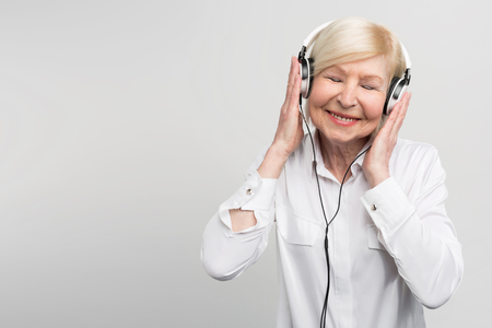 Cheerful aged woman listening to music in headphones. She is enjoying the moment. Isolated on white background. Stockfoto