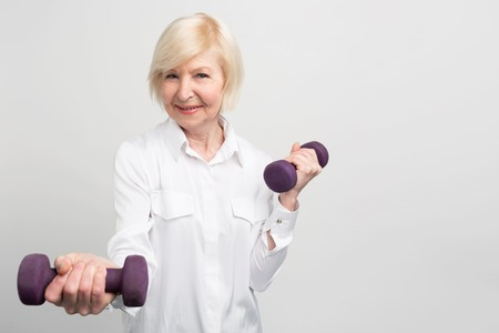 Cheerful senior lady exercising with light weights. She likes to do that because after exersices she feels much better. Isolated on white background.