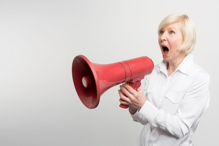 A picture of white-haired woman standing a pronouncing a speech for defencing human rights and support feminists. She is using a speaker for that purpose. Isolated on white background.