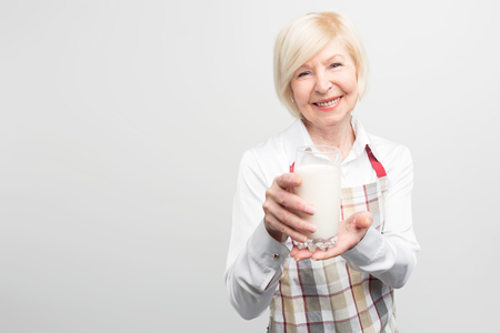 A picture where old woman wears blouse and apron and holding a cup of organic milk in her hands. She looks happy and delightful. Isolated on white background.