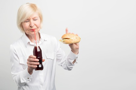 A picture of old woman tasting coca cola. and eating a burger. She doesnt like to have a healthy lifestyle. She prefers to eat tasty but fatning and bad food. Isolated on white background.