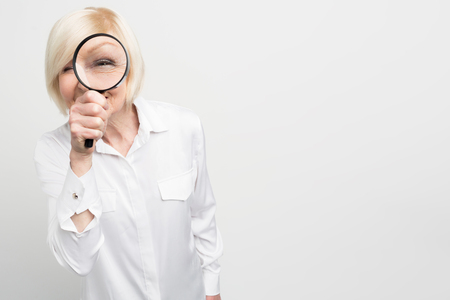 Close up of suspicious old woman in white blouse looking straight ahead through the reading glass. She looks strange. Cut view. Isolated on white background.