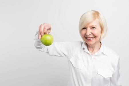 A beautiful mature woman holding a green apple in right hand. She likes to eat fruit. This is her choice. Isolated on white background. Stock Photo