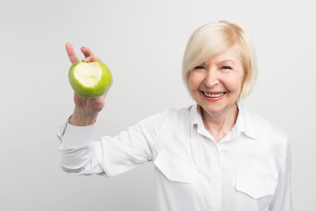 A beautiful mature woman holding a bitten green apple in right hand. She wants to show that she has a good and stron teeth. Isolated on white background. Фото со стока