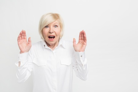 Close up of a woman in white blouse standing at the right side of frame and shwoing her hands with some screaming. She is seriously surprised. Isolated on white background.