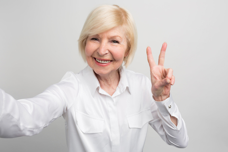 A picture of confident and modern granma that likes to take selfies. She knows everything about new trands in the world. And her age is not interfers with it. Isolated on white background.