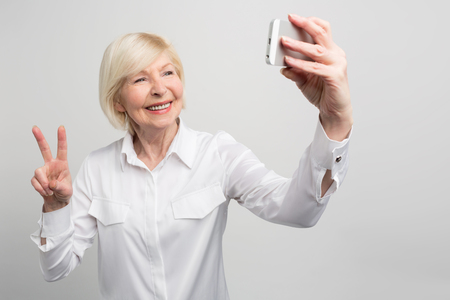 A picutre from another angle where grandma is taking a selfie. She knows everything about youths trends and use them everywhere. She is a very modern old woman. Isolated on white background. Stok Fotoğraf - 97180095