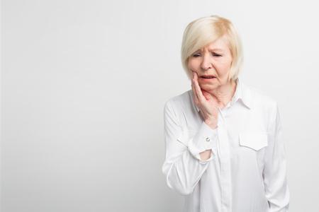 Alte Dame leidet unter Zahnschmerzen. Es fing plötzlich an zu schmerzen. Sie muss zum Zahnarzt gehen. Isoliert auf weißem hintergrund