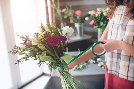 Female florist at work: pretty young dark-haired woman making fashion modern bouquet of different flowers. Women working with flowers in workshop Stock Photo