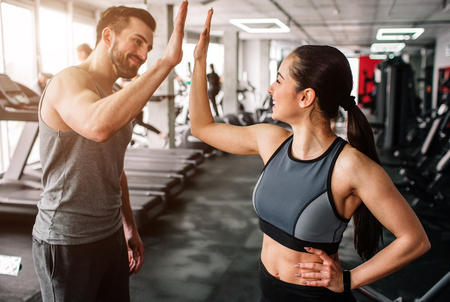 A beautiful girl and her well-built boyfriend are greeting each other with a high-five. They are happy to see each othr in the gym. Young people are ready to start their workout. Фото со стока - 97145284