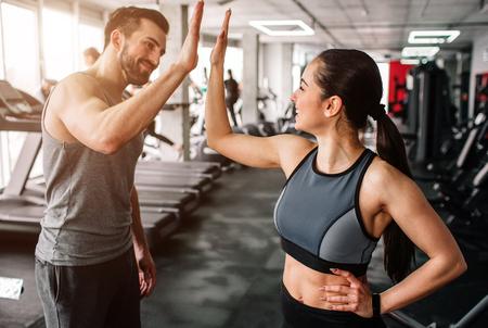 Une belle fille et son petit ami bien bâti se saluent avec un high-five. Ils sont heureux de se voir dans la salle de gym. Les jeunes sont prêts à commencer leur entraînement.