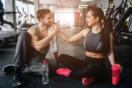 Sweet and tender picture of two beloved people sitting on the floor in the gym close to each other. They look lovely and happy to be together