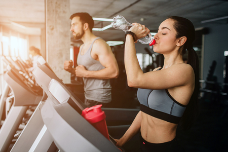 Beautiful and well-built girl is running on the running machine besides her sport partner and drinking water from the bottle while young man is just having workout