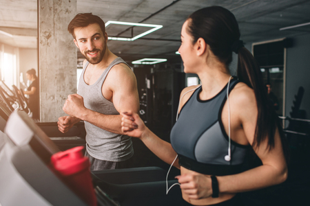 Nice picture of two cheerful people hacving the same workout on the running machine. Besides working they are talking with each other, smiling and having fun.
