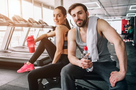 Close up of a beautiful couple sitting on the sport bench and posing. Also they are drinking water from their bottles and having rest after hard workout. Stock Photo