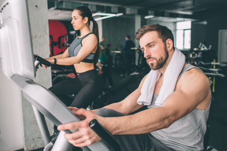 Close up of two young people training on the exercise bike. They look serious and concentrated on the workout.