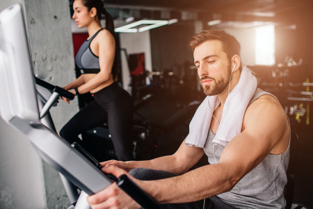 Close up of a guy wokring on the exercise bike and his girfriend doing the same thing further down. Both of them are serious and concentrated. Stock Photo