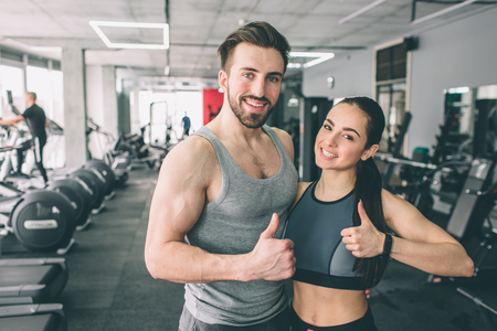Trainer and her student are standing in the sport clubs training room together and showing their big thumbs up. They are happy to exsercise in this fitness club. Young couple is smiling.