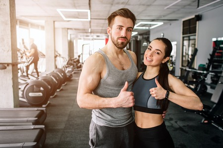 A picture of a couple standing in the sport clubs training room together and showing their big thumbs up. They are happy to exsercise in this fitness club. Young couple is smiling.
