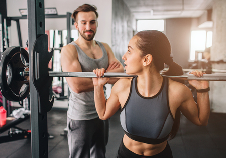 Close up of a girl wants to have some squats in Smiths machine. She is looking to her trainer because she wants to have some support from him. The guy is looking to her student with confidence. Stock Photo