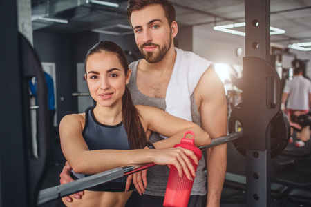 Fantastic couple is standing together in the training room and posing on camera. They look good together. This couple is having some rest after hard workout.