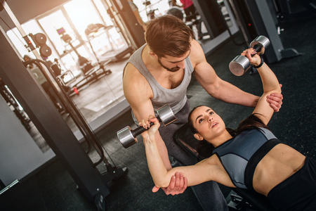Handsome guy standing near his girlfriend and helping her to do exersices with a dumbbell. He is supporting her to make sure she will not harm heerself. Stock Photo