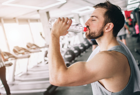 Close up of a handsome guy drinking water from the bottle and looking straight forward. He is having some rest after workout. Cut view