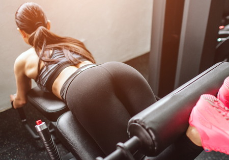 A picture of beautiful girl bending legs in machine. She is concentrated and serious. Close up. Cut view.