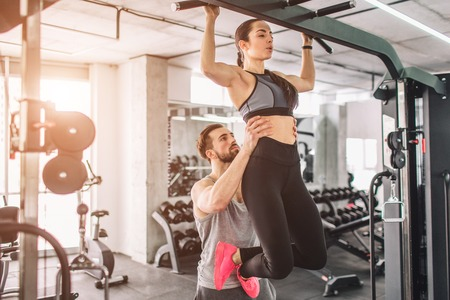 Trainer and his student is in the gy. He is helping her to pull up. THis is a part of big list of exercises. Banco de Imagens