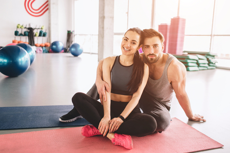 Beautiful shot of two folks that like crossfit. They are sitting together and posing on camera. Girl is smiling while the guy is looks serious.