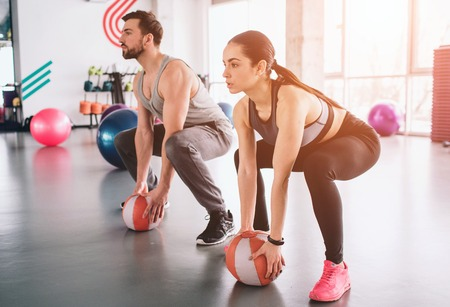 Strong guy and a slim girl are sitting in a position, ready to do squats. They have put their hands on balls ready to take them and hold it over their hands in any time.
