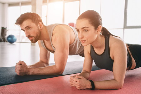 A picture from a different angle where two beautiful people are wokring out and using a plank position for that. Both of them are looking straight forward. Close up. Cut view. Stock Photo