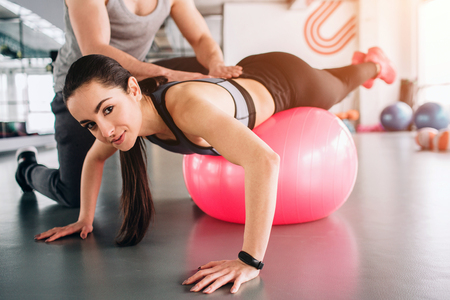 Close up and cut view of a girl that is lying on the big fitness ball and looking straight ahead. Her trainer is trying to make her back stay in a straight position.