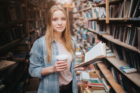 Young and beautiful student in the library. She holds a cup of coffee in right hand and a book in left one. Girl is reading an interesting book. Stock Photo