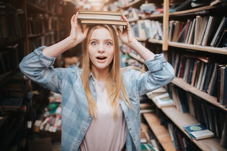 Funny picture of girl standing near bookshelf. She is holding two books on her head with her hands and looking straight forward. She looks amazed. Banco de Imagens