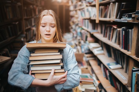 Girl is carrying a lot of books in her hands. It is hard for her to do. She looks hepless and tired. The girl stands in big old library. Stock Photo