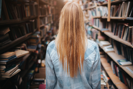 A picture og girl walking among bookshelfs with new and olb books. There is a mess everywhere in the room. She ir making a reseach.