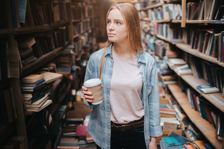 Attractive and nice girl is standing among big and long bookshelfs with old books. She is holding a cup of coffe in her hand and looking to the shelf. The woman is looking for a book.